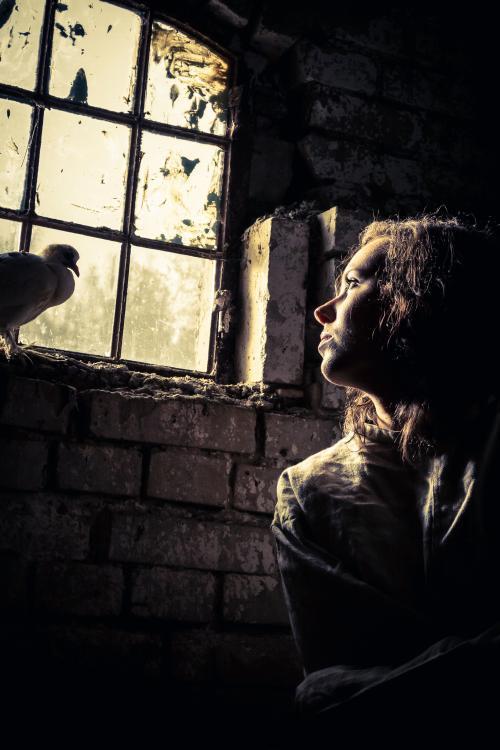 femeie-intr-o-casa-veche-privind-pe-geam